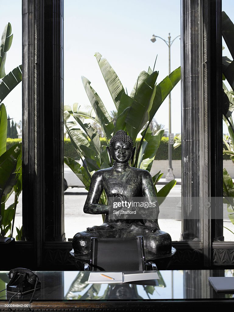 Desk with Buddha statue in background : Stock Photo
