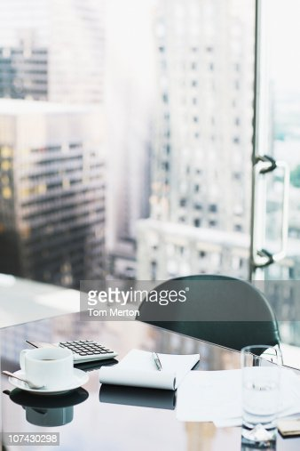 Desk with coffee, calculator, notepad and water : Stock Photo