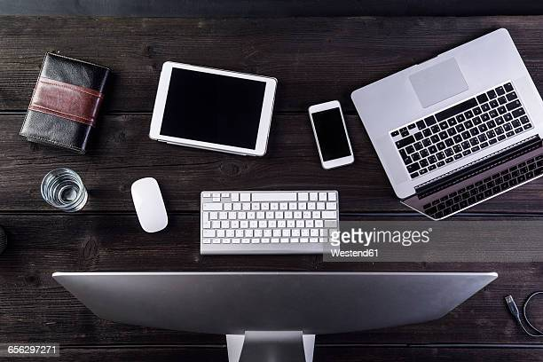 Desk with computer and various digital gadgets, overhead view