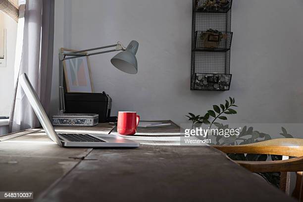 Desk with laptop and coffee cup at home office