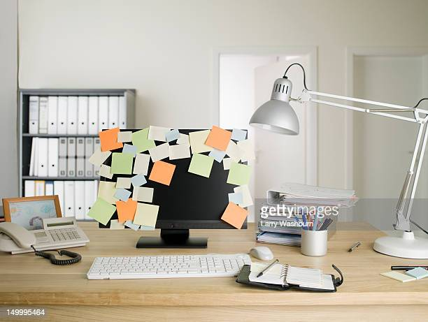 A desktop PC with blank adhesive notes all over the monitor