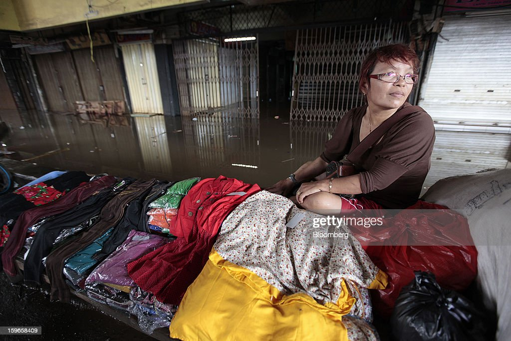 Desmaniar, a vendor, waits for customers at her stall standing in floodwaters at the Cipulir market in Jakarta, Indonesia, on Friday, Jan. 18, 2013. Indonesia declared a state of emergency in Jakarta as flooding brought traffic to a standstill in the city of 9.6 million people and swamped the offices of President Susilo Bambang Yudhoyono. Photograph by: Dimas Ardian/Bloomberg via Getty Images