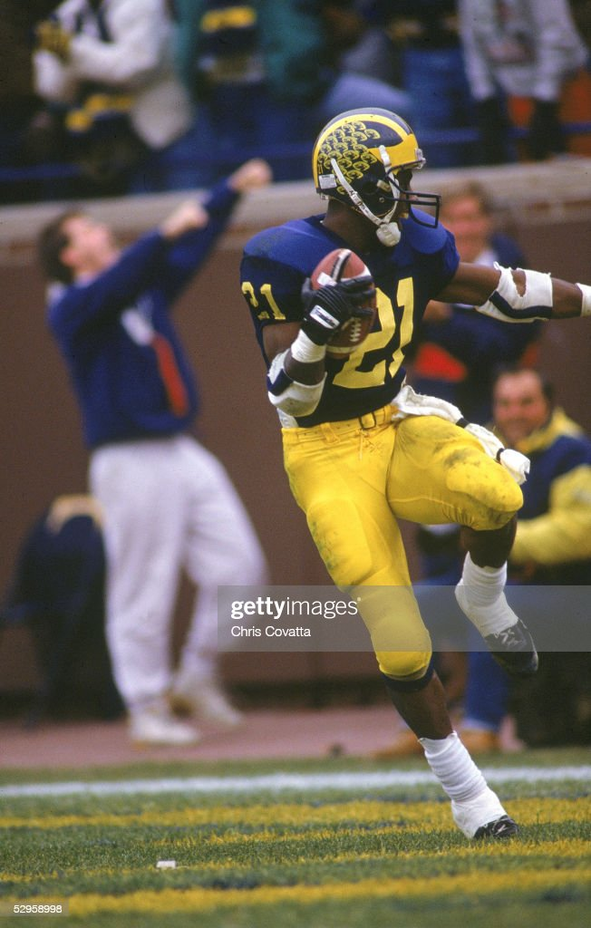 Desmond Howard of the Michigan Wolverines runs in the the 'Heisman' pose right after making a 93 yard touchdown against Ohio State circa 1991 in Ann...