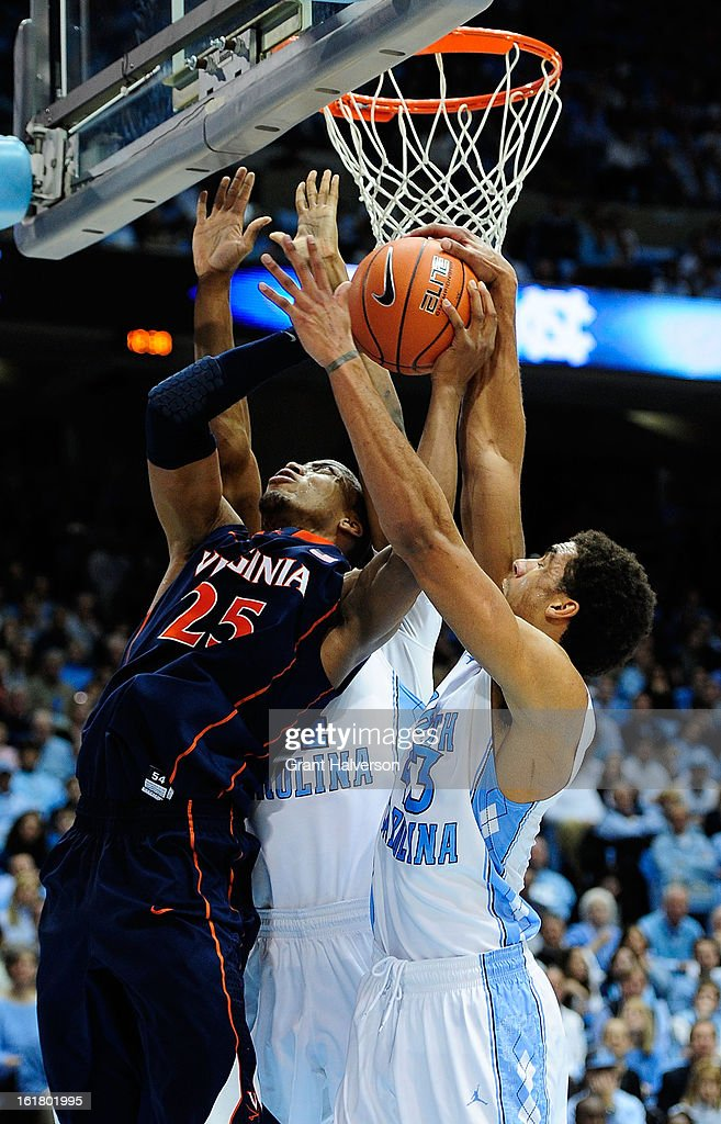 Desmond Hubert #14 and James Michael McAdoo #43 of the North Carolina Tar Heels block a shot by Akil Mitchell #25 of the Virginia Cavaliers during play at the Dean Smith Center on February 16, 2013 in Chapel Hill, North Carolina. North Carolina won 93-81.