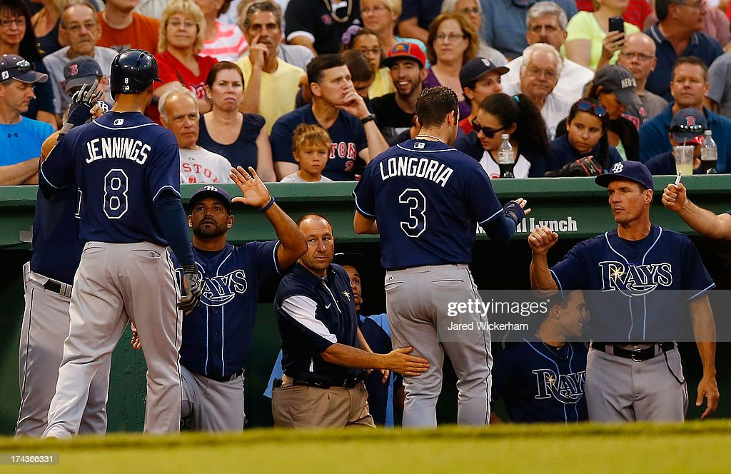 Desmond Jennings #8 and Evan Longoria #3 of the Tampa Bay Rays are congratulated by teammates in the dugout after scoring in the third inning against the Boston Red Sox during the game on July 24, 2013 at Fenway Park in Boston, Massachusetts.