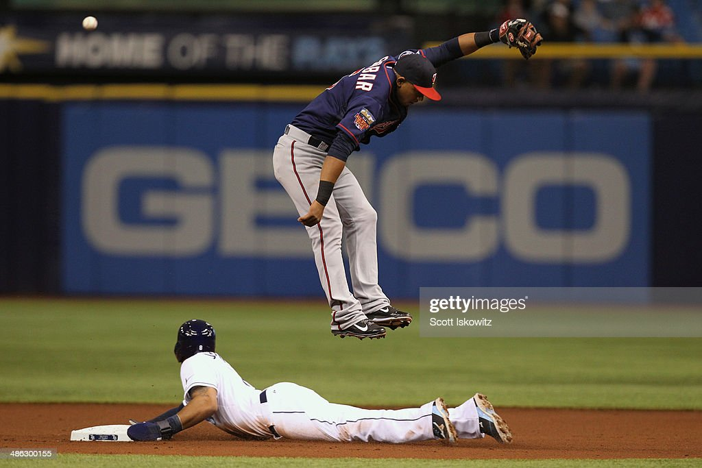 <a gi-track='captionPersonalityLinkClicked' href=/galleries/search?phrase=Desmond+Jennings&family=editorial&specificpeople=5974085 ng-click='$event.stopPropagation()'>Desmond Jennings</a> #8 of the Tampa Bay Rays slides into second base as <a gi-track='captionPersonalityLinkClicked' href=/galleries/search?phrase=Eduardo+Escobar&family=editorial&specificpeople=7522733 ng-click='$event.stopPropagation()'>Eduardo Escobar</a> #5 of the Minnesota Twins misses the throw during the 1st inning at Tropicana Field on April 23, 2014 in St Petersburg, Florida. <a gi-track='captionPersonalityLinkClicked' href=/galleries/search?phrase=Desmond+Jennings&family=editorial&specificpeople=5974085 ng-click='$event.stopPropagation()'>Desmond Jennings</a> #8 of the Tampa Bay Rays advance to third base on the error.
