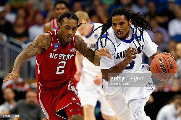 Desmond Lee of the North Carolina State Wolfpack grabs a loose ball against Anthony Barber of the North Carolina State Wolfpack in the second half...