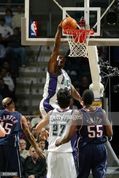 Desmond Mason of the Milwaukee Bucks dunks as Vince Carter of the New Jersey Nets Zaza Pachulia of the Milwaukee Bucks and Jabari Smith of the New...