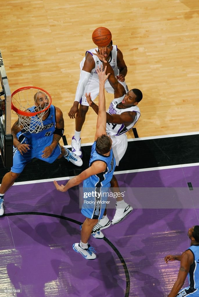 Desmond Mason of the Sacramento Kings hooks a shot over Mehmet Okur of the Utah Jazz during the preseason game on October 23 2009 at Arco Arena in...