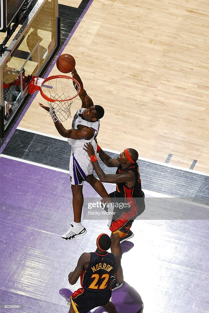 Desmond Mason of the Sacramento Kings shoots a layup against Stephen Jackson and Anthony Morrow of the Golden State Warriors during a preseason game...