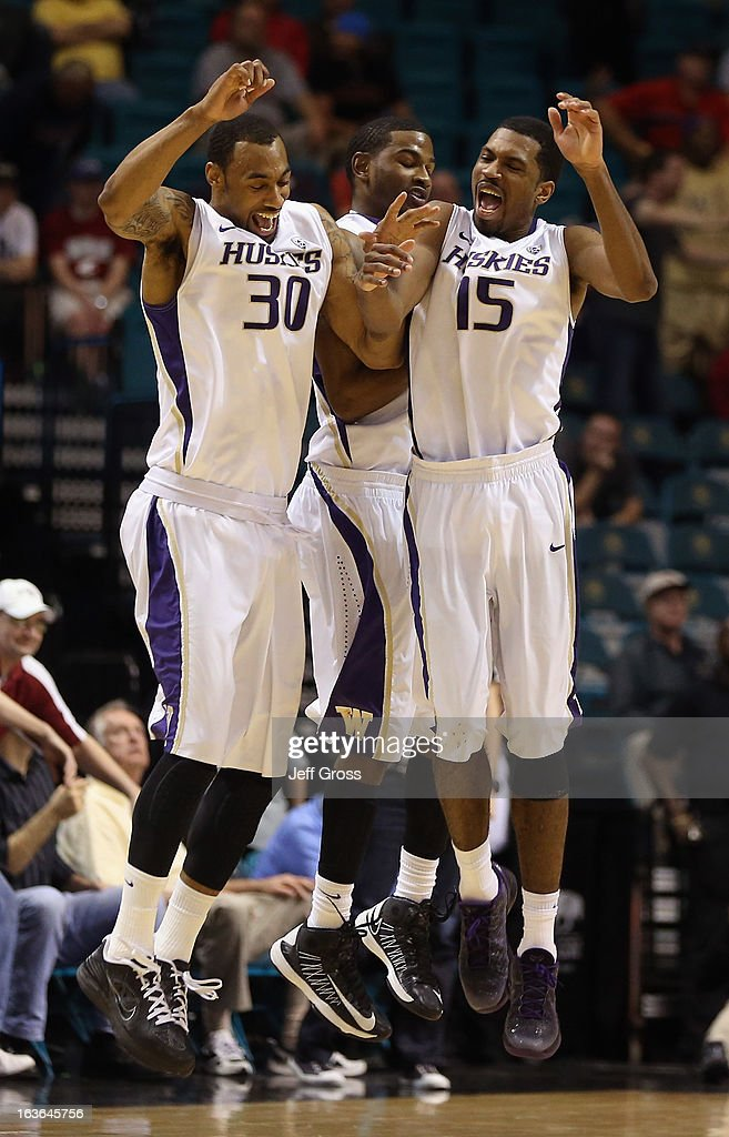 Desmond Simmons #30, C.J. Wilcox #23 and Scott Suggs #15 of the Washington Huskies celebrate their teams 64-62 victory over the Washington State Cougars during the first round of the Pac 12 Tournament at the MGM Grand Garden Arena on March 13, 2013 in Las Vegas, Nevada.