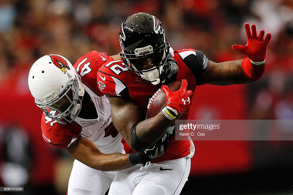 Desmond Trufant #21 of the Atlanta Falcons is tackled by Marcus Cooper #41 of the Arizona Cardinals during the first half at the Georgia Dome on November 27, 2016 in Atlanta, Georgia.