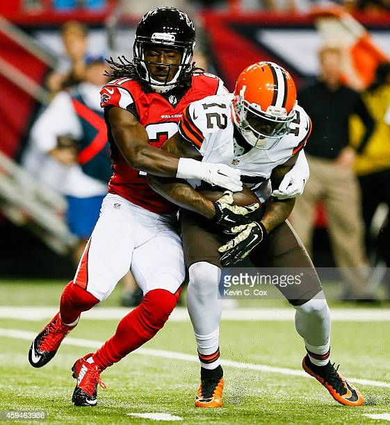 Desmond Trufant of the Atlanta Falcons tackles Josh Gordon of the Cleveland Browns in the first half at Georgia Dome on November 23 2014 in Atlanta...