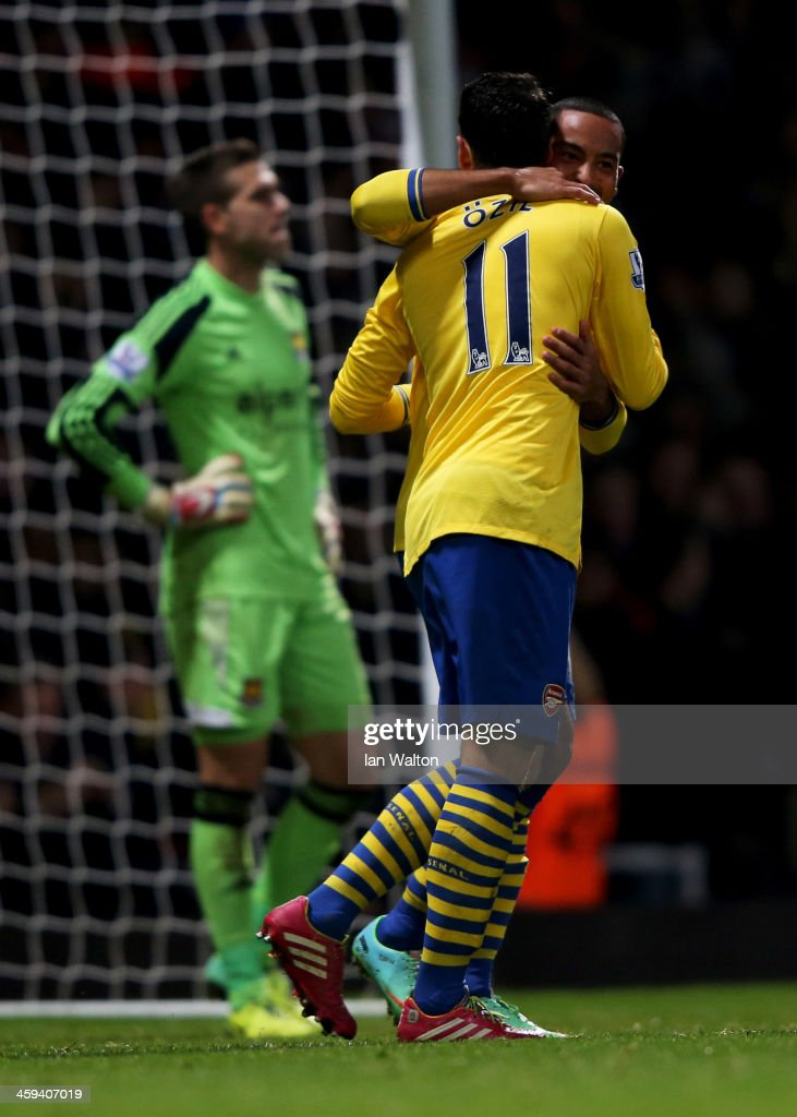 Despair for Adrian of West Ham United (L) as Theo Walcott of Arsenal (R) celebrates with Mesut Oezil (11) as he scores their first goal during the Barclays Premier League match between West Ham United and Arsenal at Boleyn Ground on December 26, 2013 in London, England.