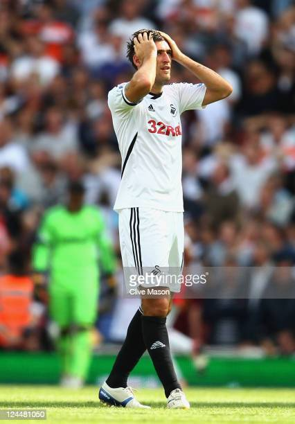 Despair for Danny Graham of Swansea City as Andrey Arshavin of Arsenal scores their first goal during the Barclays Premier League match between...