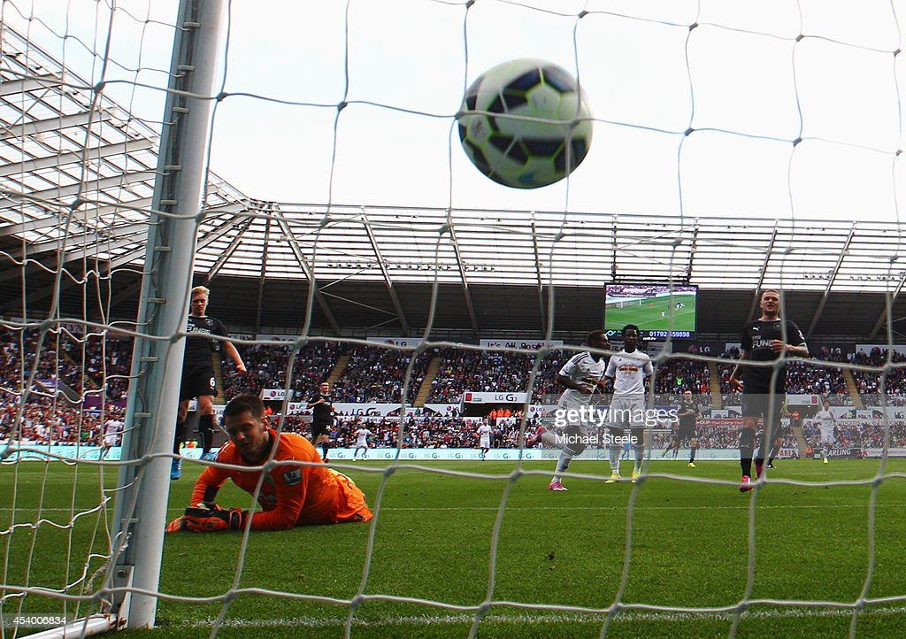 Despair for golakeeper Thomas Heaton of Burnley as Nathan Dyer of Swansea City (C) scores their first goal during the Barclays Premier League match between Swansea City and Burnley at Liberty Stadium on August 23, 2014 in Swansea, Wales.