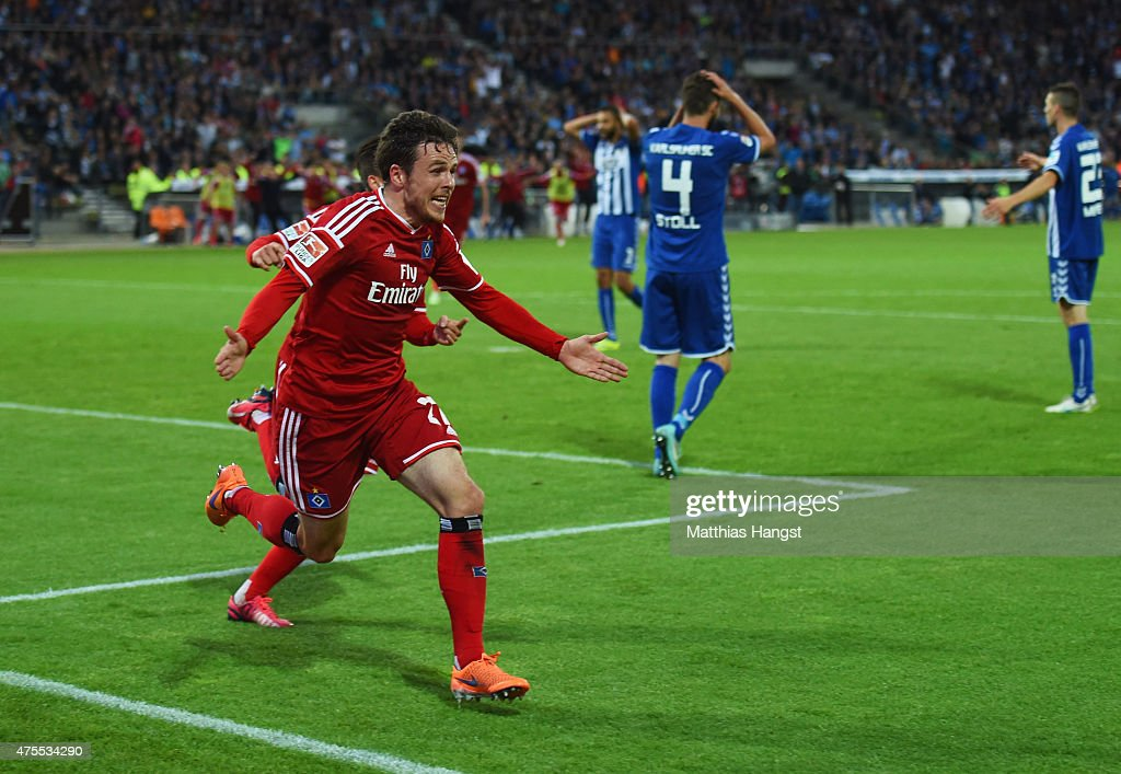 Despair for Karlsruher SC defenders as <a gi-track='captionPersonalityLinkClicked' href=/galleries/search?phrase=Nicolai+Mueller&family=editorial&specificpeople=2344337 ng-click='$event.stopPropagation()'>Nicolai Mueller</a> of Hamburger SV (27) celebrates as he scores their second goal during the Bundesliga play-off second leg match between Karlsruher SC and Hamburger SV on June 1, 2015 in Karlsruhe, Germany.