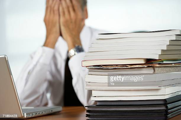 Despaired businessman using a laptop a stack of documents next to him