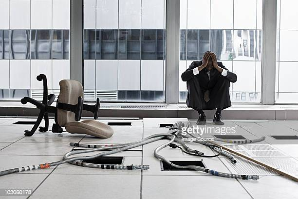 Despairing businessman in abandoned office