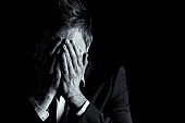 Low-key portrait of desperate office manager in dark suit covering his face with both hands, black & white conversion isolated on black background with copy-space.