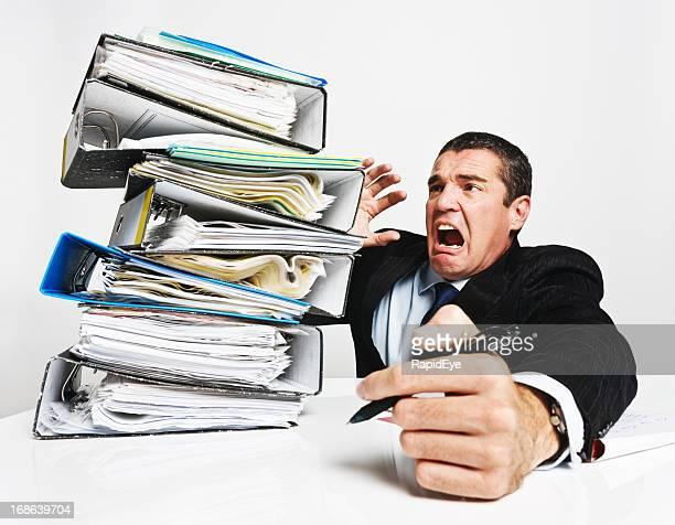 Ein verzweifelter executive mit riesigen und teetering Stapel von Dateien