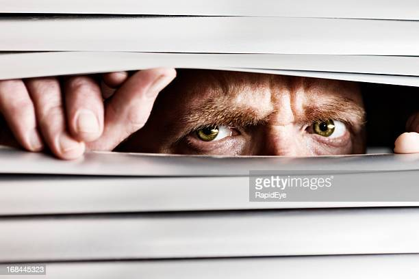Desperate frowning man peeping out through venetian blinds