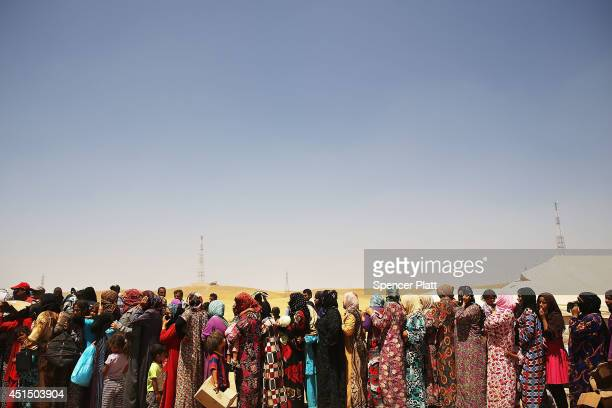 Desperate Iraqi women at the Khazair displacement camp for those caughtup in the fighting in and around the city of Mosul wait for food and other...