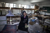 A desperate Palestinian woman throws debris in the air at the classroom where she is taking shelter with her family on July 30 2014 following Israeli...