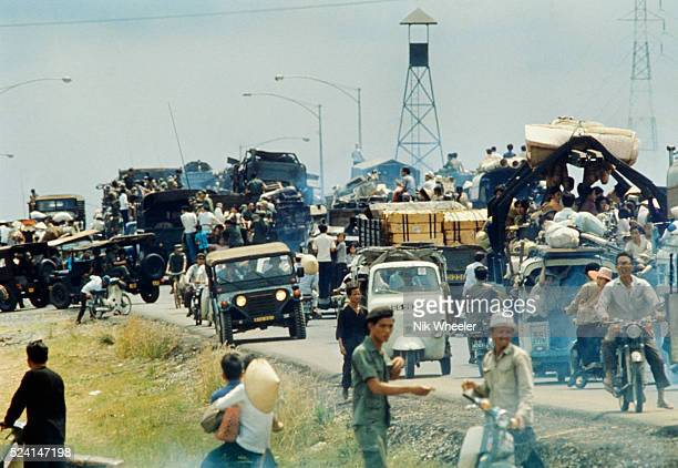 Desperate South Vietnamese refugees cling to vehicles along Highway 1 as they flee North Vietnamese troops advancing to capture Saigon a few days...