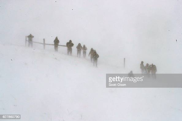 Despite blizzard conditions activists watch from a hillside as military veterans march in support of the 'water protectors' at Oceti Sakowin Camp on...