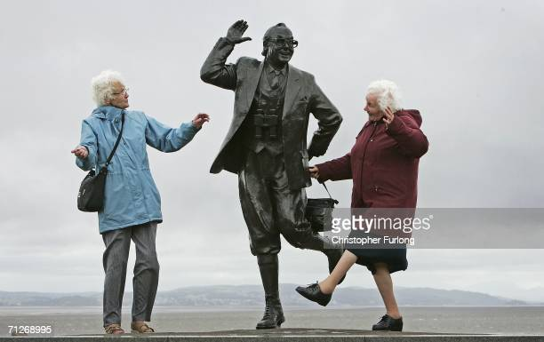 Despite inclement weather pensioners raise a happy smile as they perform the famously British dance of comedians Morcambe and Wise next to a statue...