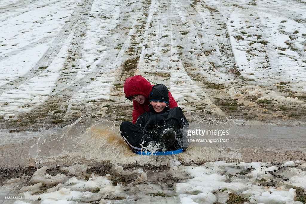 Despite the pouring rain, Evan Hall, 10, front and Quinn Buckley, 11, both of Silver Spring, didn't want to miss what could be their last day of the season to sled. They plowed down a partially snow covered hill in Takoma Park, MD, right into a giant mud puddle.