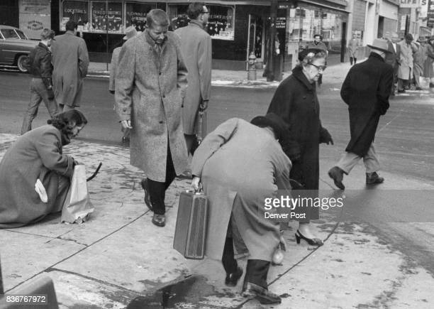 Despite walk light opportunity and luggage handicap unidentified man reaches for rolling grapefruit to help Denver Post reporter Lynn Lilliston who...