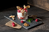 Dessert in glass with raspberries, curd, yoghurt, dried apple, almond slivers and chocolate sauce
