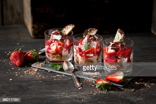 Dessert in glasses with yoghurt, curd, strawberries, chocolate chips and chocolate marshmallow