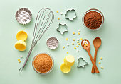 Dessert ingredients and utensils on green pastel background. Top view