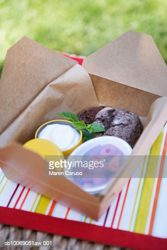 Desserts in a container ready to be eaten sitting on a picnic basket : Stock Photo