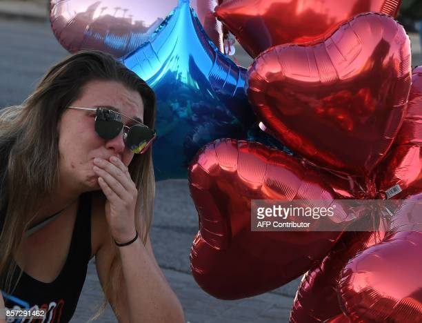 Destiny Alvers who attended the Route 91 country music festival and helped rescue her friend who was shot reacts at a makeshift memorial near the...