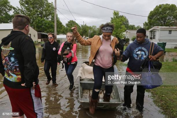 Destiny Harris is helped out of a boat by Tyshon Sykes at the Village Green Estates trailer park on Monday May 1 in Cedar Hill Mo Residents of the...