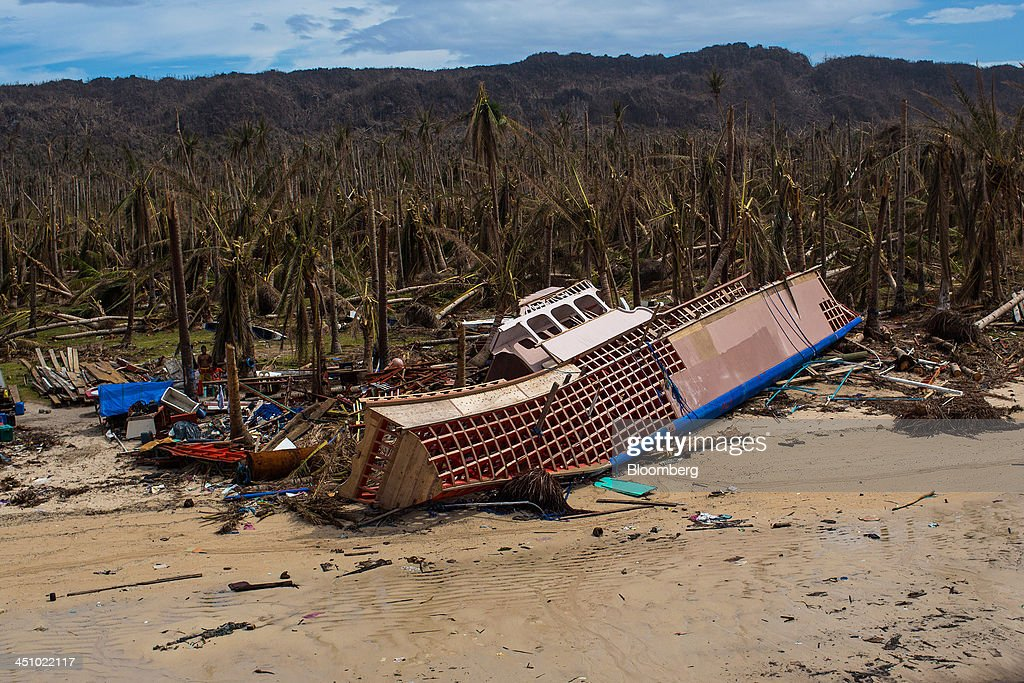 A destroyed boat lies among debris on a beach near Sulyan Village on the coastline of Eastern Samar, the Philippines, on Wednesday, Nov. 20, 2013. Super Typhoon Haiyan slammed into the central Philippines on Nov. 8, knocking down most buildings, killing thousands, displacing 4 million people and affecting more than 10 million. Photographer: Julian Abram Wainwright/Bloomberg via Getty Images
