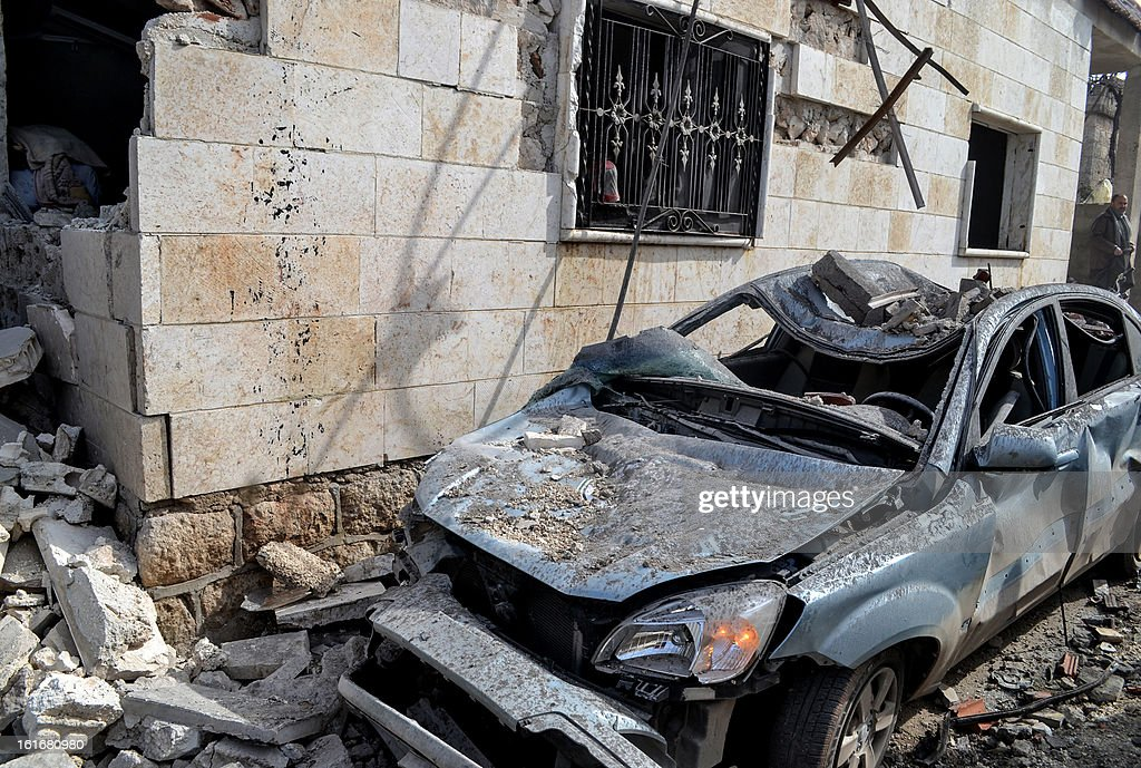 A destroyed car is seen next to a house that was bombed in an airstrike on the Syrian town of Hass, west of Maarat al-Numan, in the northern province of Idlib, where more than 10 people were killed, including four children, on February 14, 2013. As prospects faded for a political solution to the war that has killed nearly 70,000, UN chief Ban Ki-moon called on the Security Council to overcome its paralysis and take 'meaningful' action to stop the bloodshed. AFP PHOTO / STR
