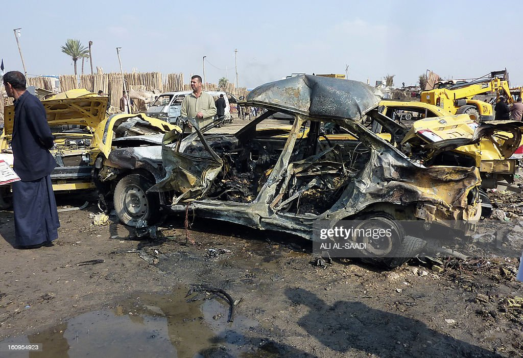 A destroyed car lies at the scene of a explosion at the bird market in the north Baghdad Shiite neighbourhood of Kadhimiyah on February 8, 2013. A spate of car bombs in Shiite areas of Iraq, including two blasts minutes apart at a popular bird market, killed at least 29 people, the latest in a spike in violence amid a political crisis. The attacks, which left nearly 70 others wounded, primarily targeted marketplaces that are often crowded on Fridays, the weekly holiday in Iraq, and took the death toll from a week of violence to more than 100. AFP PHOTO/ ALI AL-SAADI