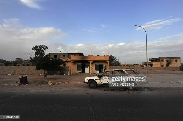 A destroyed car sits outside abandoned houses in the Libyan town of Tawarga on September 25 2011 The people of Tawarga who are mostly blackskinned...
