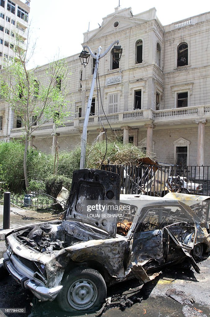 A destroyed car sits outside the Syrian Interior Ministry following a bomb blast in the Marjeh district of Damascus on April 30 , 2013. A blast in the central Damascus district of Marjeh killed at least 14 people, Syrian state television reported, a day after a Prime Minister Wael al-Halqi survived a bomb attack elsewhere in the capital .
