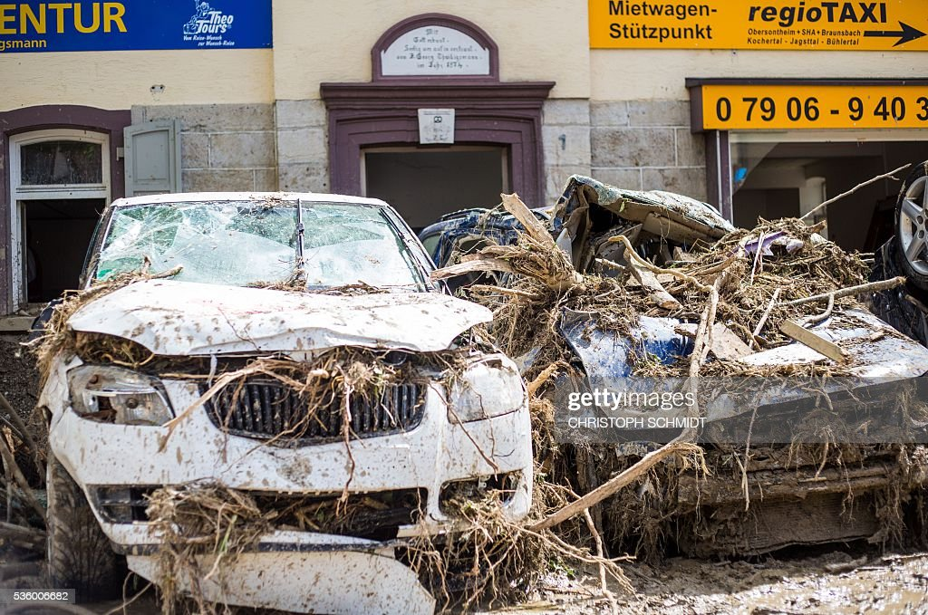 Destroyed cars covered in mud and rubble are seen on May 31 2016 in Braunsbach southern Germany hit by the floods after a thunderstorm Cleanup...