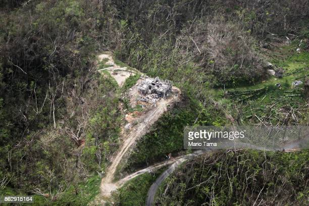 A destroyed home is viewed from the air amidst damaged and destroyed trees during recovery efforts four weeks after Hurricane Maria struck on October...