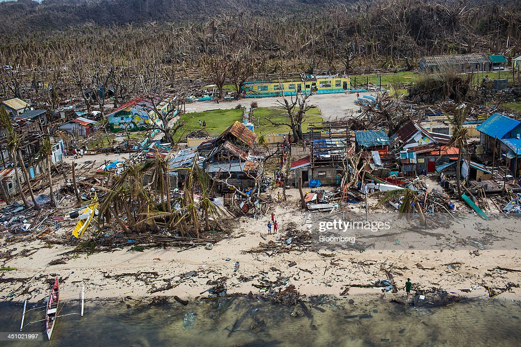 Destroyed houses and palm trees stand in Sulyan Village on the coastline of Eastern Samar, the Philippines, on Wednesday, Nov. 20, 2013. Super Typhoon Haiyan slammed into the central Philippines on Nov. 8, knocking down most buildings, killing thousands, displacing 4 million people and affecting more than 10 million. Photographer: Julian Abram Wainwright/Bloomberg via Getty Images