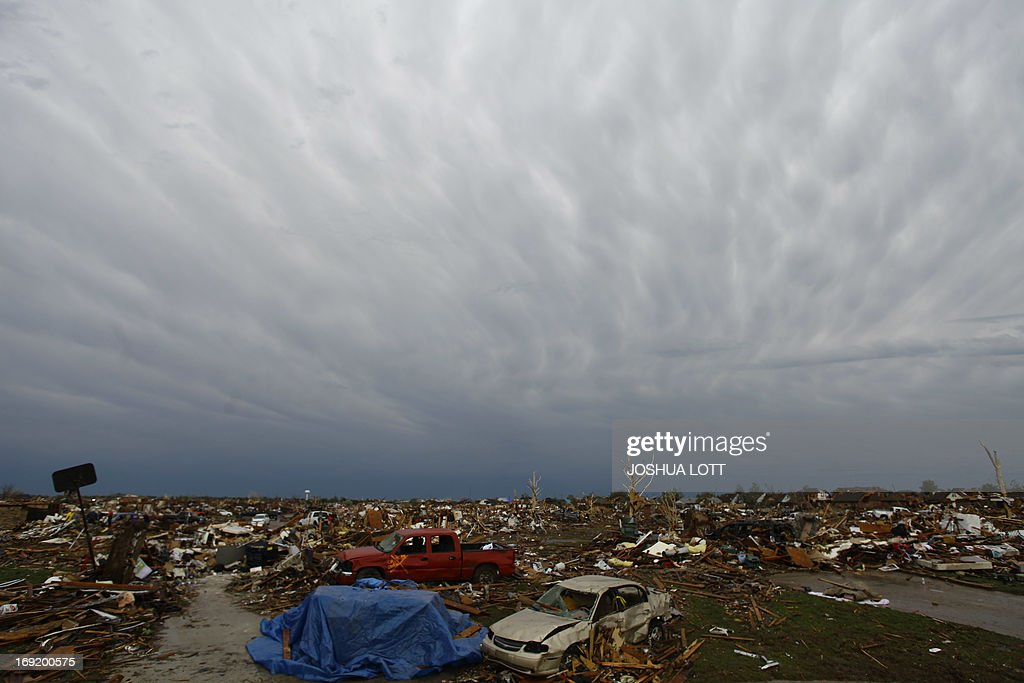 Destroyed houses and vehicles sit untouched on May 21, 2013 in Moore, Oklahoma. Families returned to a blasted moonscape that had been an American suburb Tuesday after a monstrous tornado tore through the outskirts of Oklahoma City, killing at least 24 people. Nine children were among the dead and entire neighborhoods vanished, with often the foundations being the only thing left of what used to be houses and cars tossed like toys and heaped in big piles. AFP PHOTO/Joshua LOTT