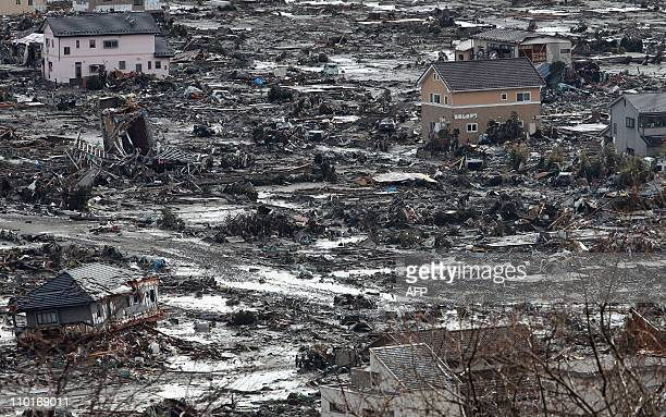 Destroyed houses stand amongst a scene of destruction at Ishinomaki city in Miyagi prefecture on March 16 2011 The official toll of the dead and...