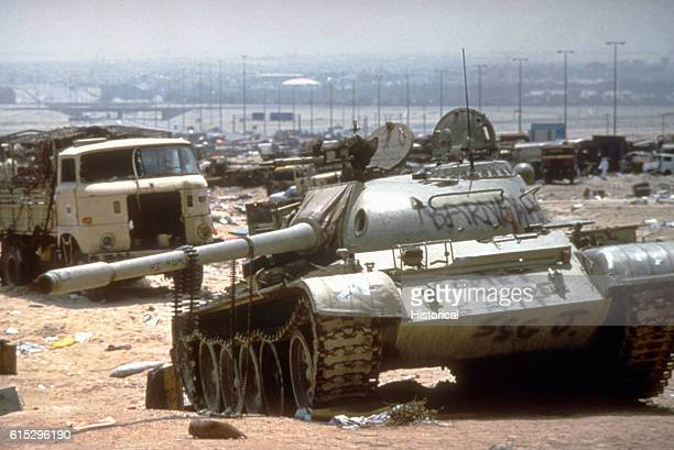 A destroyed Iraqi T55 main battle tank painted with graffiti by Coalition troops lies amidst other destroyed vehicles along the highway between...
